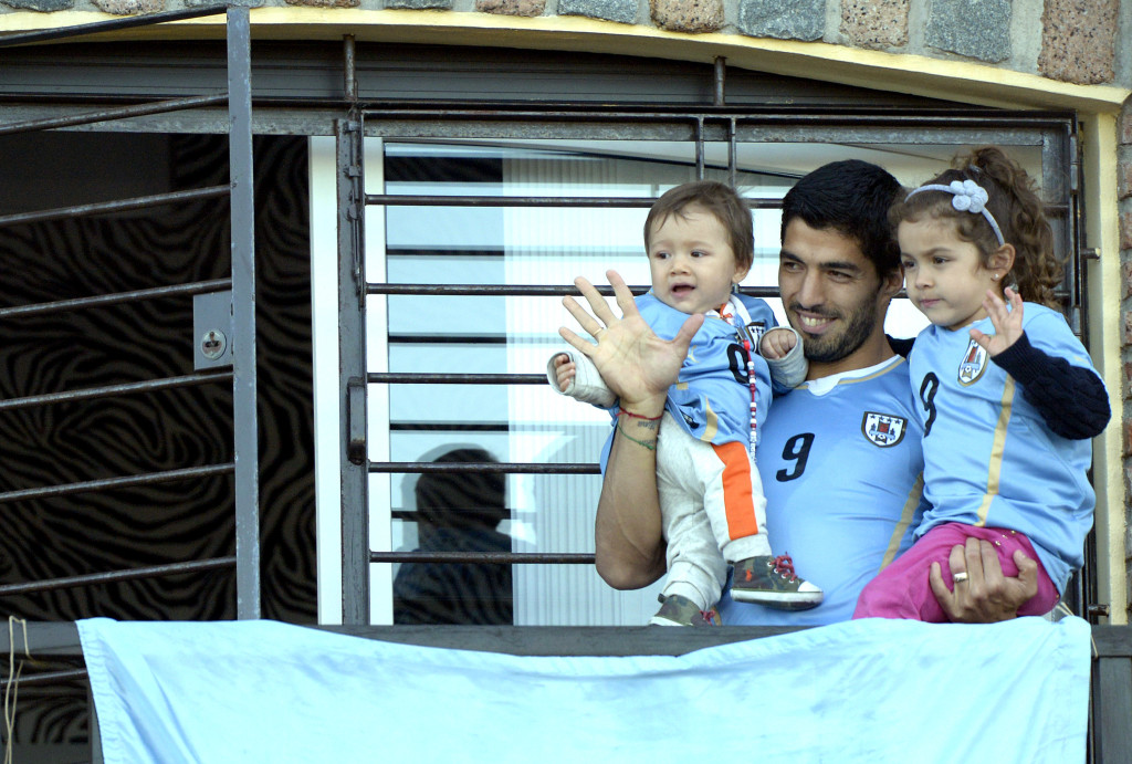 Uruguay's soccer player Luis Suarez, center, with his children Benjamin, left, and Delfina, waves to fans from his home, before the start of his team's World Cup round 16 match with Colombia, on the outskirts of Montevideo, Uruguay, Saturday, June 28, 2014. FIFA banned Suarez from all football activities for four months for biting an opponent at the World Cup.