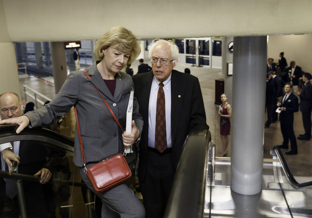 Senate Veterans Affairs Committee Chairman Sen. Bernie Sanders, I-Vt., and Sen. Tammy Baldwin, D-Wis., head to the Senate chamber Wednesday. Sanders proposed legislation this week that would allow veterans who can't get timely appointments with VA doctors to go to community health centers, military hospitals or private doctors. The Associated Press