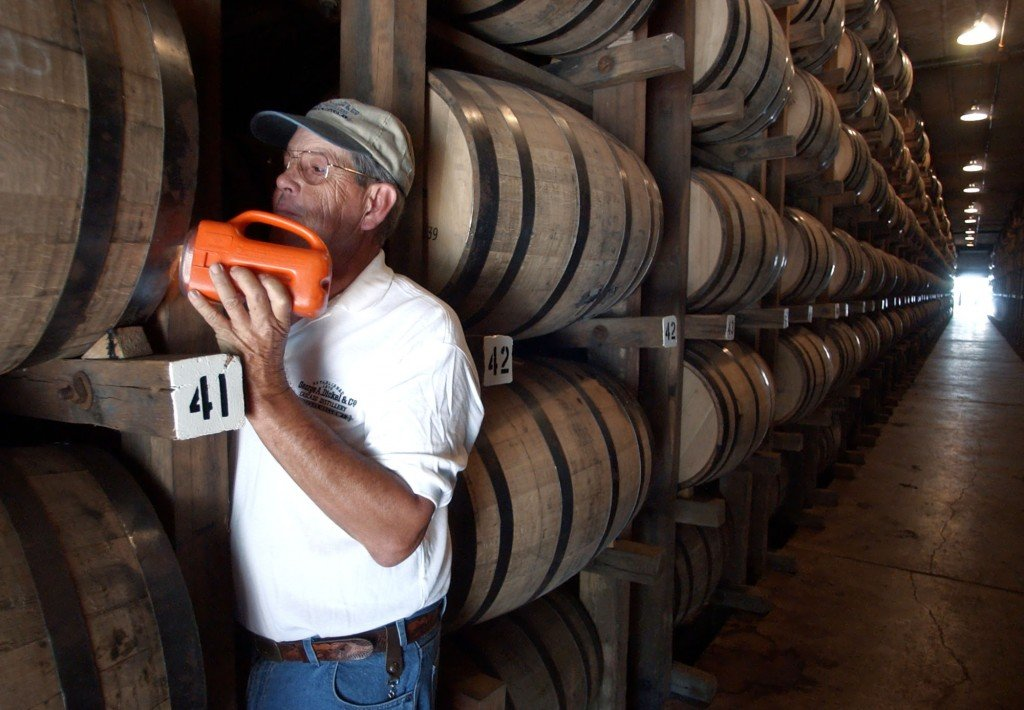 Dewayne Evans checks for leaks in the barrels of whiskey aging in a warehouse at the George Dickel Distillery near Tullahoma, Tenn., in this undated file photo.   The Associated Press