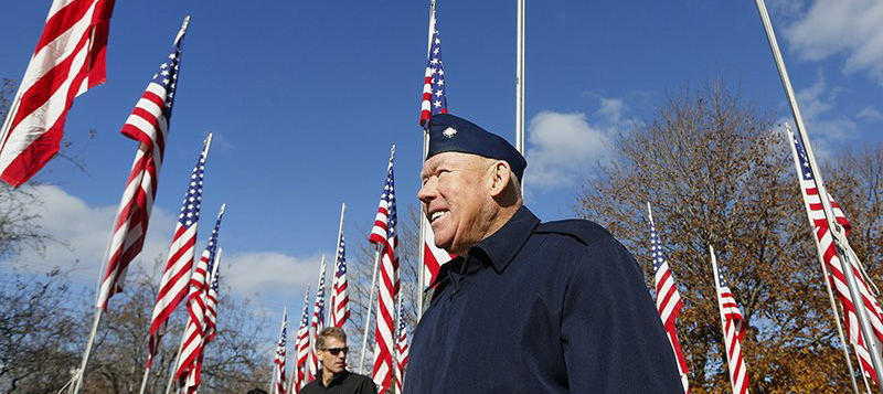 Korean War veteran Charles Tibbetts walks among flags honoring veterans after Yarmouth's 2013 Veterans Day ceremony. Federal officials failed to heed years of warnings about the U.S. veterans health care system. 2013 File Photo/Derek Davis