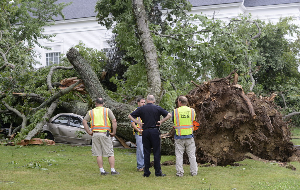 Public works employees and a York police officer look over damage next to the First Parish Church on Wednesday after a severe storm hit York.