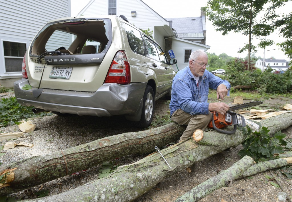 First Parish Church parishioner Sterling Brightman repairs a saw Wednesday as he joins others cleaning up a tree that damaged this car next to the church in York.