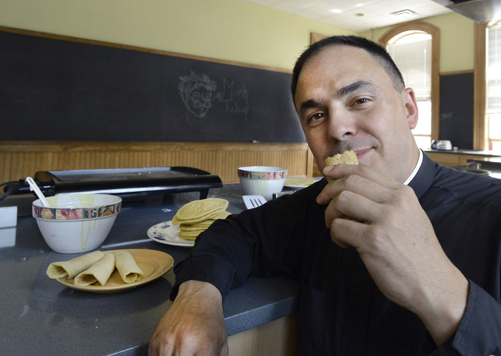 Father Paul Dumais makes ployes in a kitchen at St. Mary's Nutritional Center in Lewiston. John Patriquin/Staff Photographer