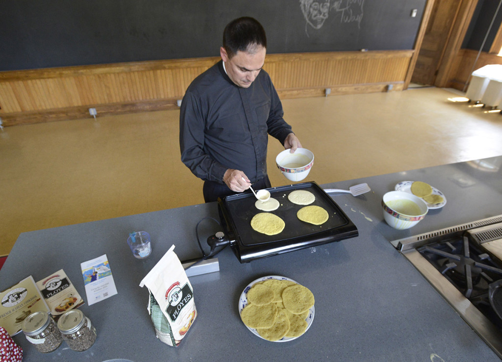 Dumais makes ployes in a kitchen at St. Mary's Nutritional Center in Lewiston.