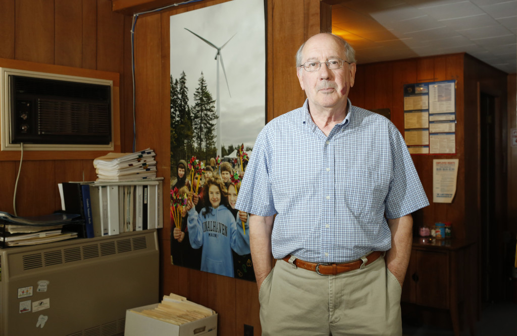 Chip Farrington, General Manager of the Fox Islands Electric Cooperative, poses for a photo in the cooperative's office next to a photo taken on the first day of the turbines started spinning.