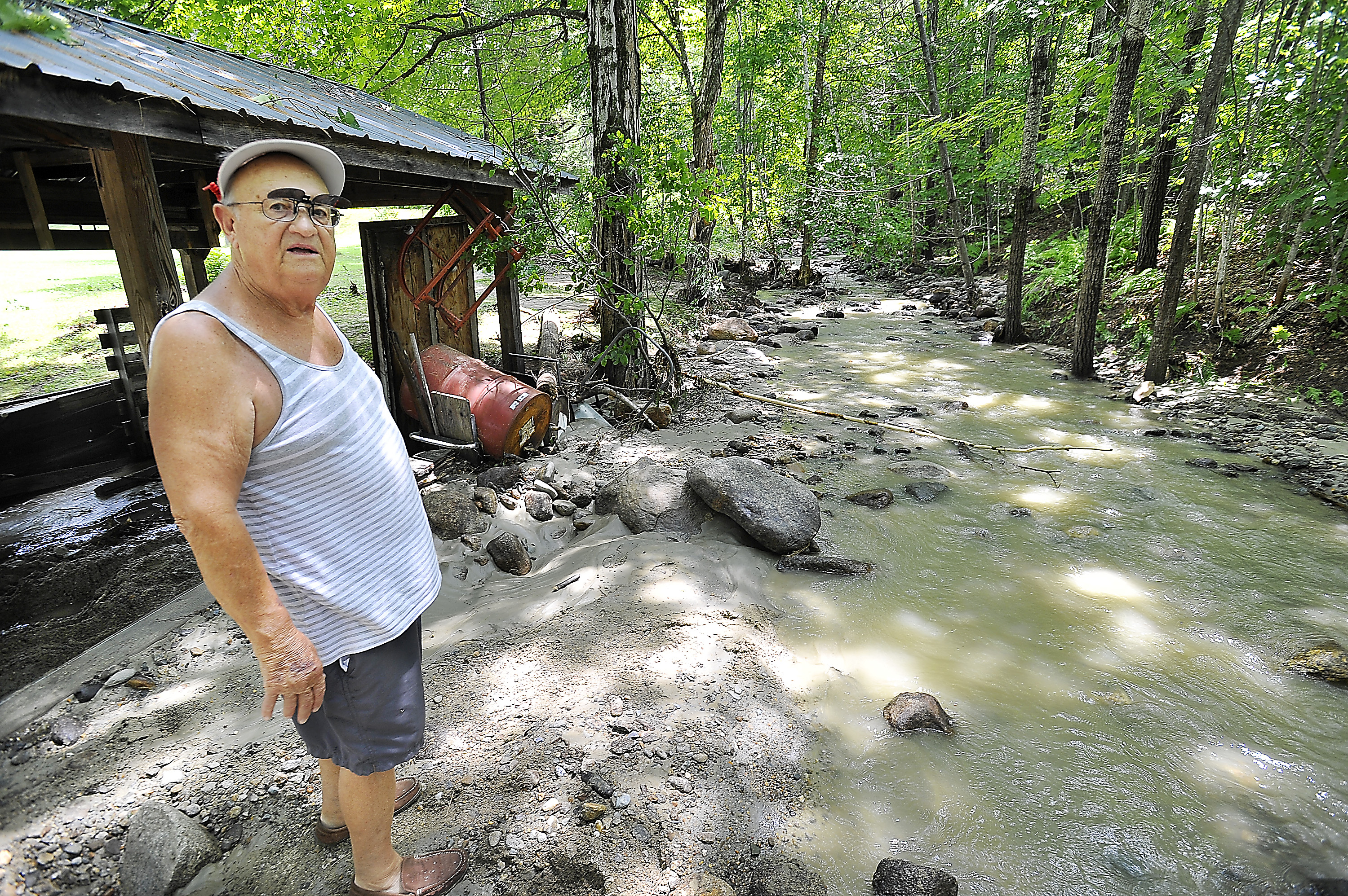 Resident Ted Orino stands by the brook that changed direction as it filled with rocks and soil in Rumford during heavy rains Wednesday night. He calculated 5 inches of rain fell in two hours at his home weather station.