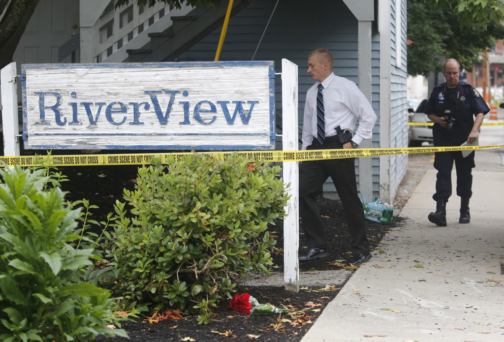 A bouquet of flowers was placed at the apartment building at 23 Water St. in Saco where Maine State Police are investigating the discovery of five bodies. Derek Davis/Staff Photographer