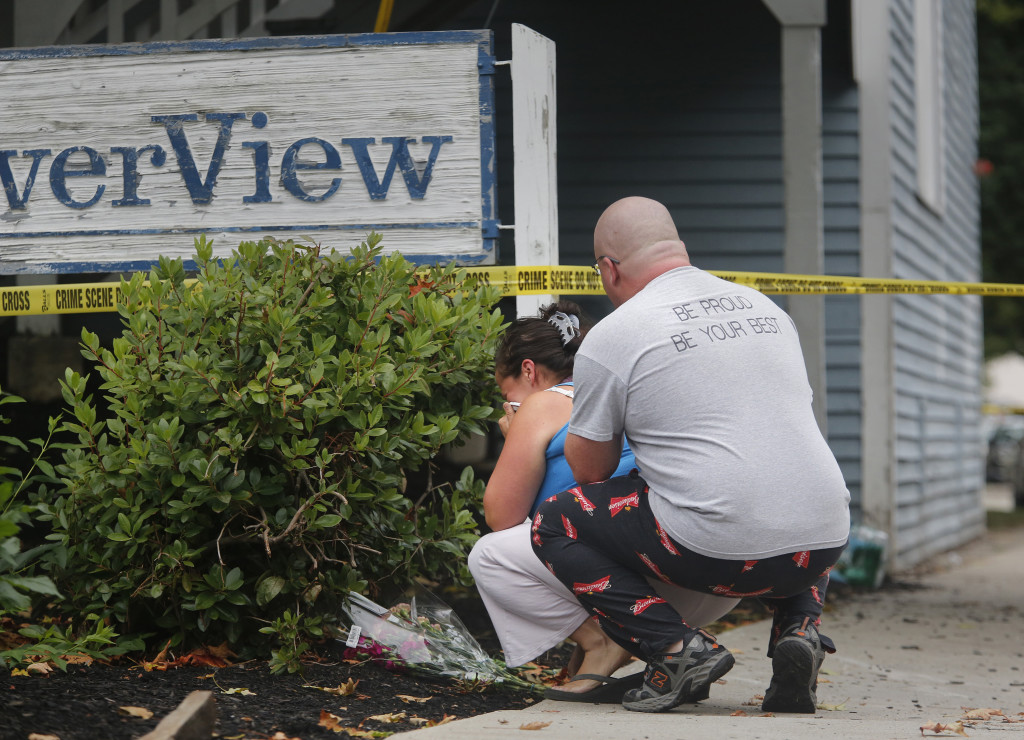 Dellas Nason of Saco comforts his wife, Heather, as she lays flowers at 23 Water St.  Heather Nason said she used to baby-sit the three children whose bodies were found Sunday. Derek Davis/Staff Photographer