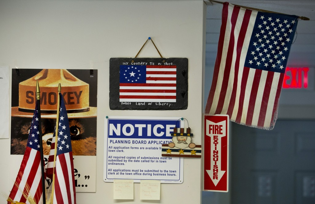The Liberty town hall displays its patriotism among notices from the Planning Board and Smokey the Bear seen Monday, June 30, 2014.