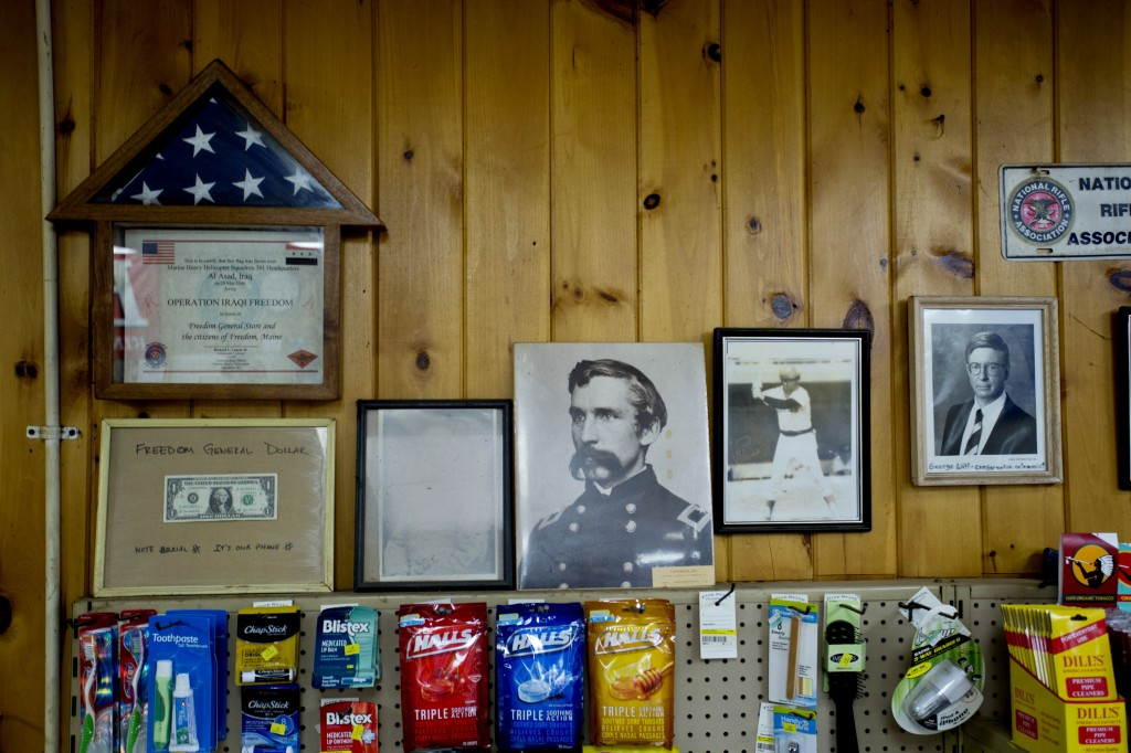 An American flag that flew over a base in Iraq, and a portrait of Union Civil War General Joshua Chamberlain, are among the patriotic touches that line the walls of the Freedom General Store in Freedom Monday, June 30, 2014.