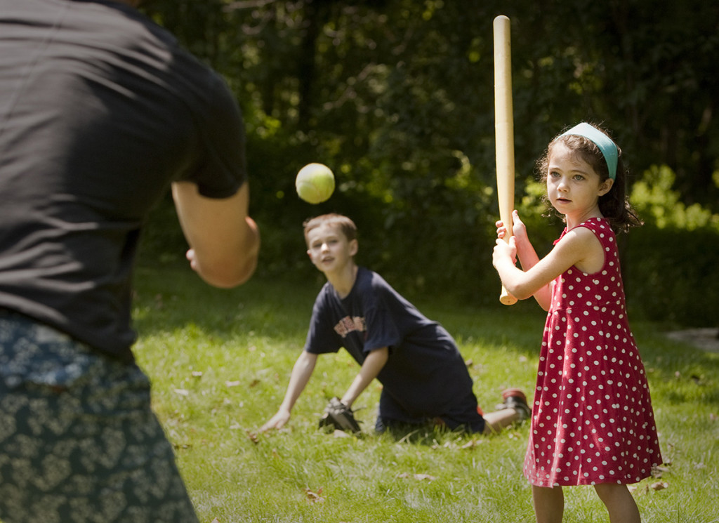 Emerson Cross, age 5 of Cape Elizabeth, takes a pitch from Portland Sea Dogs infielder Stefan Welch in her grandparent's Cape Elizabeth back yard. Her brother Mason Cross, 7, catches at center.  The children's grandparents, Beth and Dave Schroeder, are the host family for Welch and his fiancee Shannon Lodge.