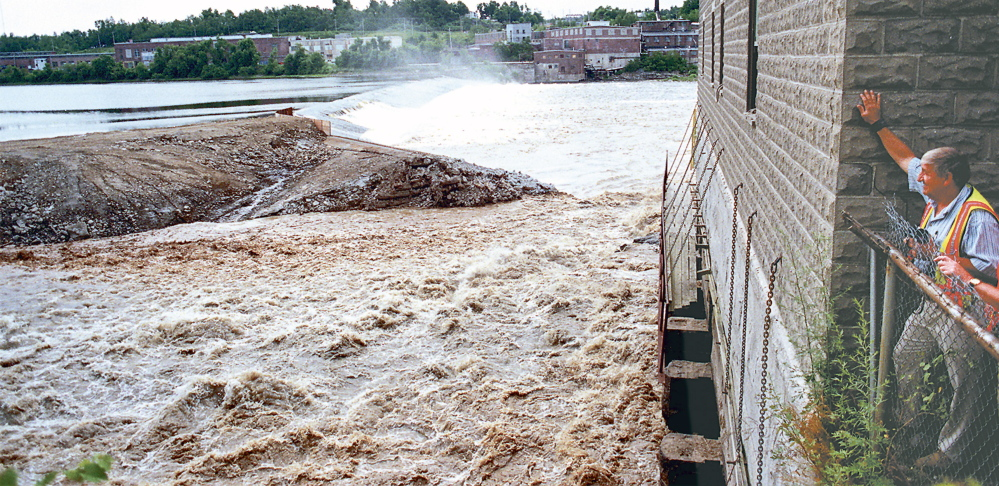 John Charest, Augusta's public works director, watches the Kennebec River flow through the breach from the Edwards Dam block house.