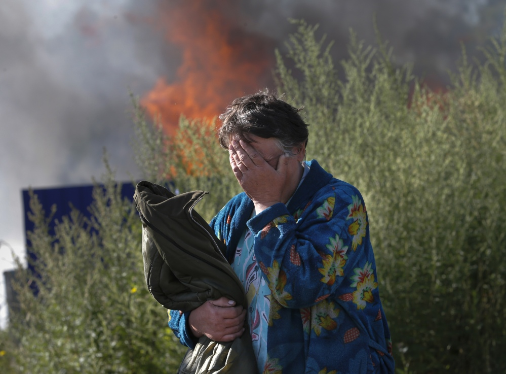 A woman cries near her burning house after shelling occurred in the city of Slovyansk, eastern Ukraine, on Monday. Continued violation of a cease-fire has led Ukraine's recently elected president to declare an offensive against pro-Russian separatists.