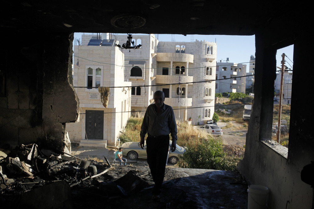 A Palestinian inspects the damaged family home of Amer Abu Aisheh, one of two Palestinians identified by Israel as suspects in the killing of three Israeli teenagers, after it was damaged by the Israeli army in the West Bank city of Hebron, Tuesday, July 1, 2014. Israeli soldiers blew up a door of Abu Aisheh's home in Hebron early Tuesday, said an Israeli military official. AP photos show extensive damage to one side of the house.