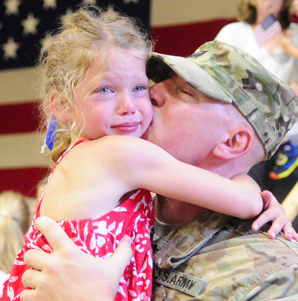 "Capt. Brian McClellan of Eliot gets a big hug from daughter Sarah Beth McClellan, 8, after the 133rd Engineer Battalion was dismissed Tuesday at the Augusta Armory. ""It feels great to be back,"" he said."