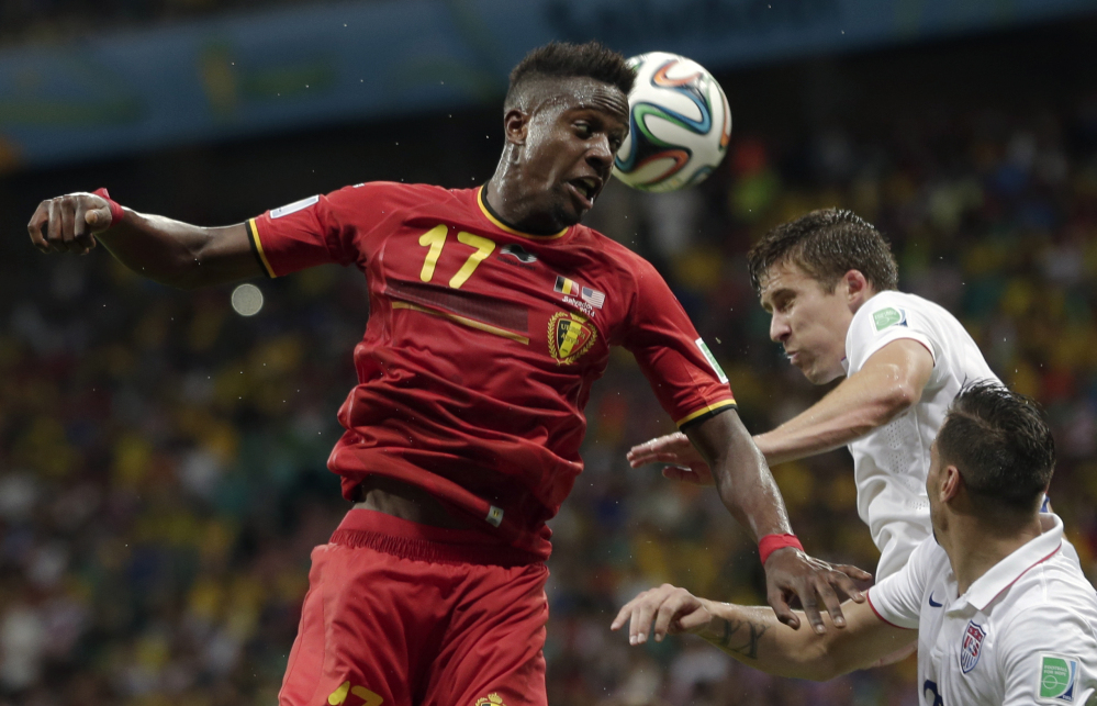Belgium's Divock Origi heads the ball over United States' Matt Besler and Geoff Cameron, right, during the World Cup round of 16 soccer match between Belgium and the USA at the Arena Fonte Nova in Salvador, Brazil, on Tuesday.
