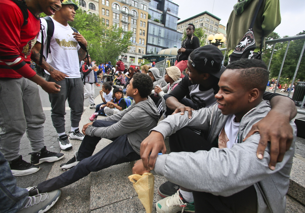 "In this June 12, 2014 photo, Andrew Sanders, right, leader of the dance troupe W.A.F.F.L.E., which stands for We Are Family For Life Entertainment, meets with members of his squad in Union Square, New York. ""We're not just knuckleheads. ... We're actually about something,"" said Saunders. (AP Photo/Bebeto Matthews)"
