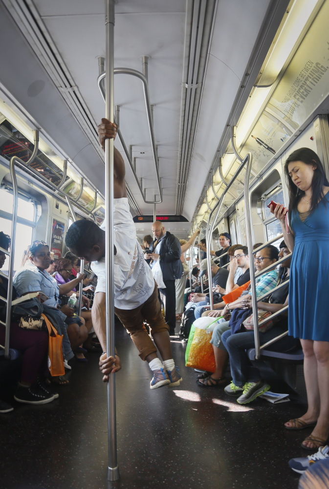 In this June 17, 2014 photo, Andrew Sanders, center, leader of the group W.A.F.F.L.E., which stands for We Are Family For Life Entertainment, performs acrobatic dance on a subway, in New York. His troupe, which has a shoe-brand sponsor and has been booked for music videos, parties, even a wedding, is reluctant to perform on subways because of police attention. (AP Photo/Bebeto Matthews)