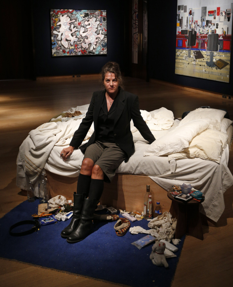 British artist Tracey Emin poses for photographers next to her 1998 artpiece, titled 'My Bed' at an auction house exhibition space in central London.