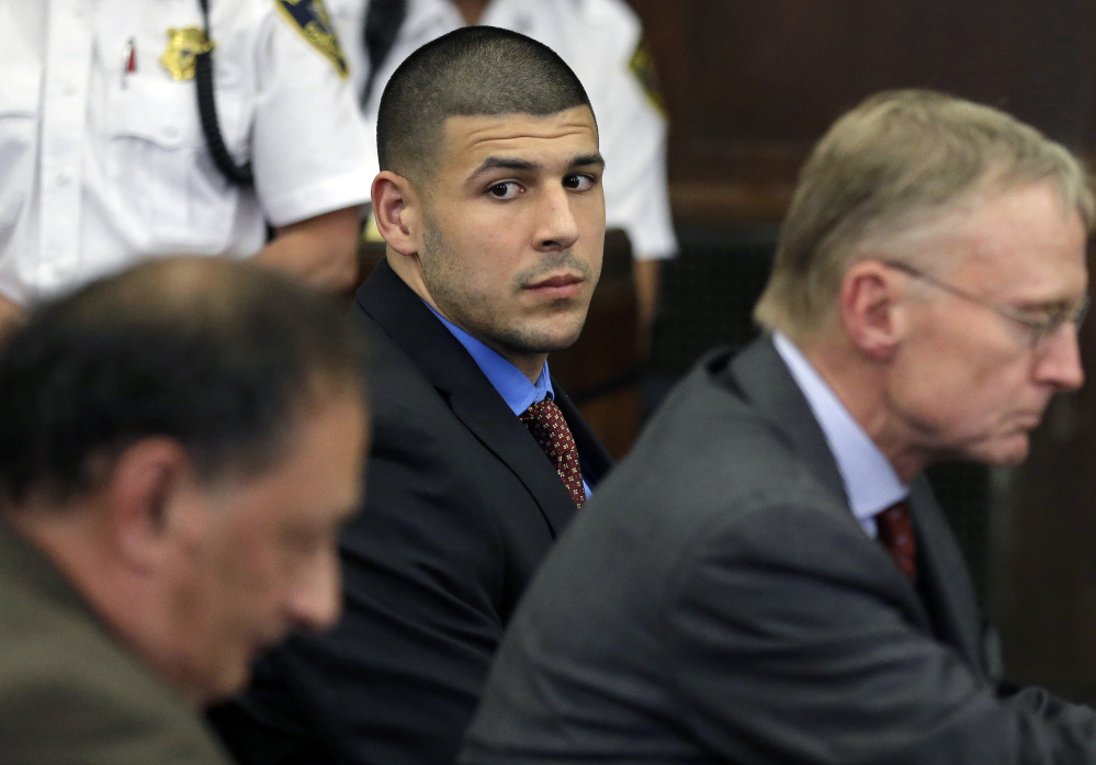 Former New England Patriots football player Aaron Hernandez, center, looks toward defense attorneys James Sultan, left, and Charlie Rankin, right, during a hearing in Suffolk Superior Court in Boston in June.