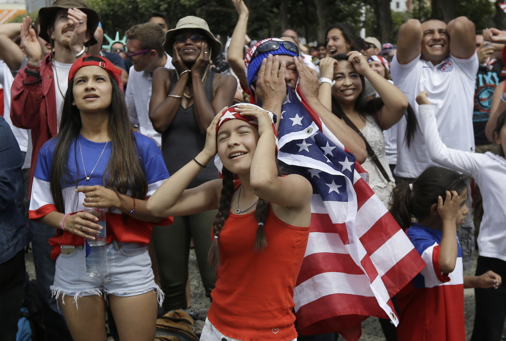 Amy Mazariegos, foreground, reacts with other United States fans as they watch the World Cup round of 16 soccer match between the United States and Belgium at a public viewing party in San Francisco, Tuesday, July 1, 2014.