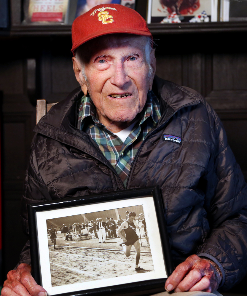 This Jan. 21, 2014 photo, Louis Zamperini displays one of his photographs as a student and sprinter, at his Los Angeles home.
