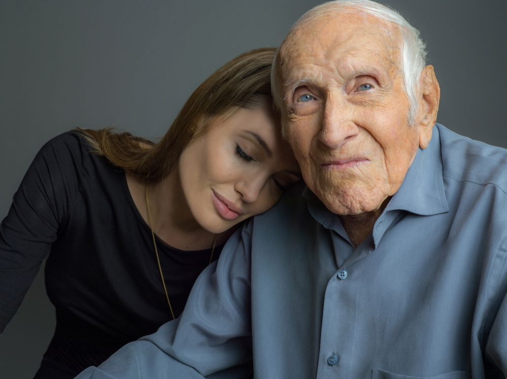 "This undated photo provided by Universal Pictures, Angelina Jolie is photographed with Louis Zamperini.  Jolie is directing the Universal movie, ""Unbroken,"" about the life of Zamperini."