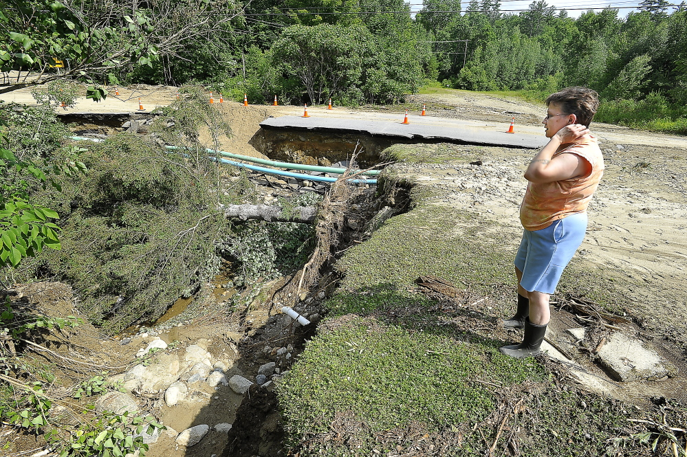 Stephenie Ackerman, who went through the heavy rains, lightning, and winds in her home on South Rumford Road with her two year-old grandson, observes the damage to her property.