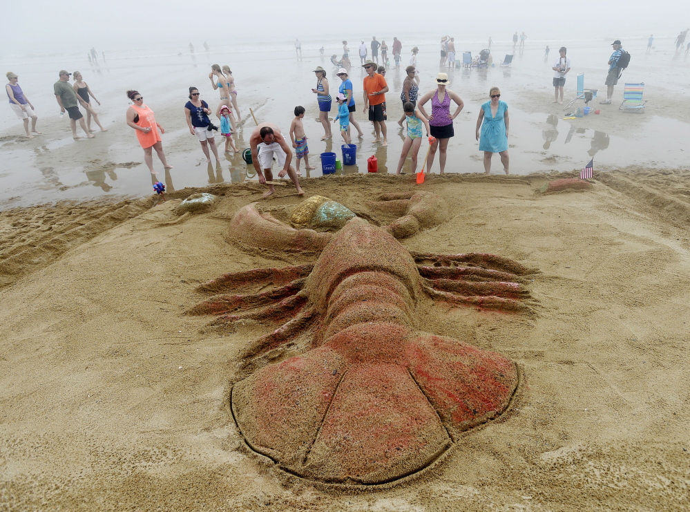 Jason Sargent, front, of Caribou puts the finishing touches on his team's sand sculpture of a lobster eating an ice cream cone.