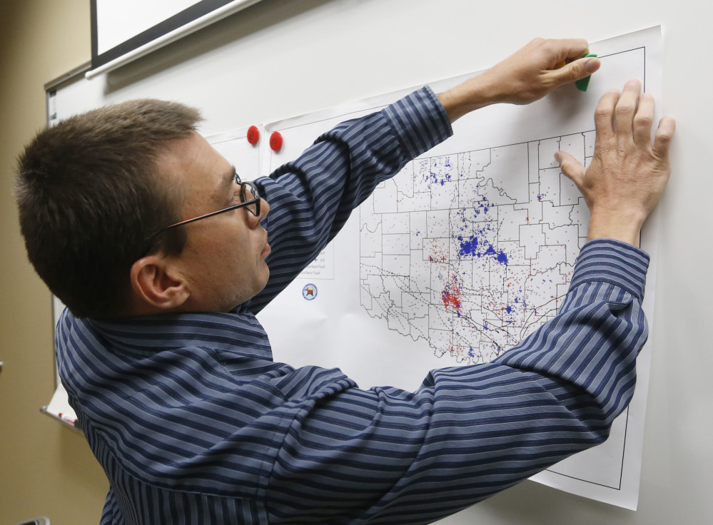 Austin Holland, research seismologist at the Oklahoma Geological Survey, hangs up a chart depicting earthquake activity at his office at the University of Oklahoma.