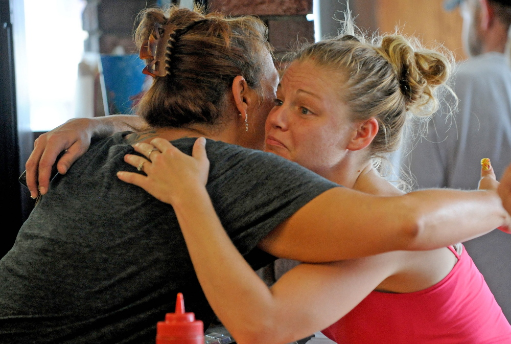 Bolley's Famous Franks manager Zena McFadden, left, gets a hug Thursday from loyal customer Lindsey Doyle at the eatery in Waterville.
