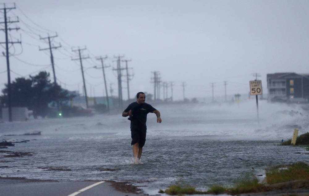 A man crosses a flooded Highway 64 as wind pushes water over the road as Hurricane Arthur passes through Nags Head, N.C., on Friday.