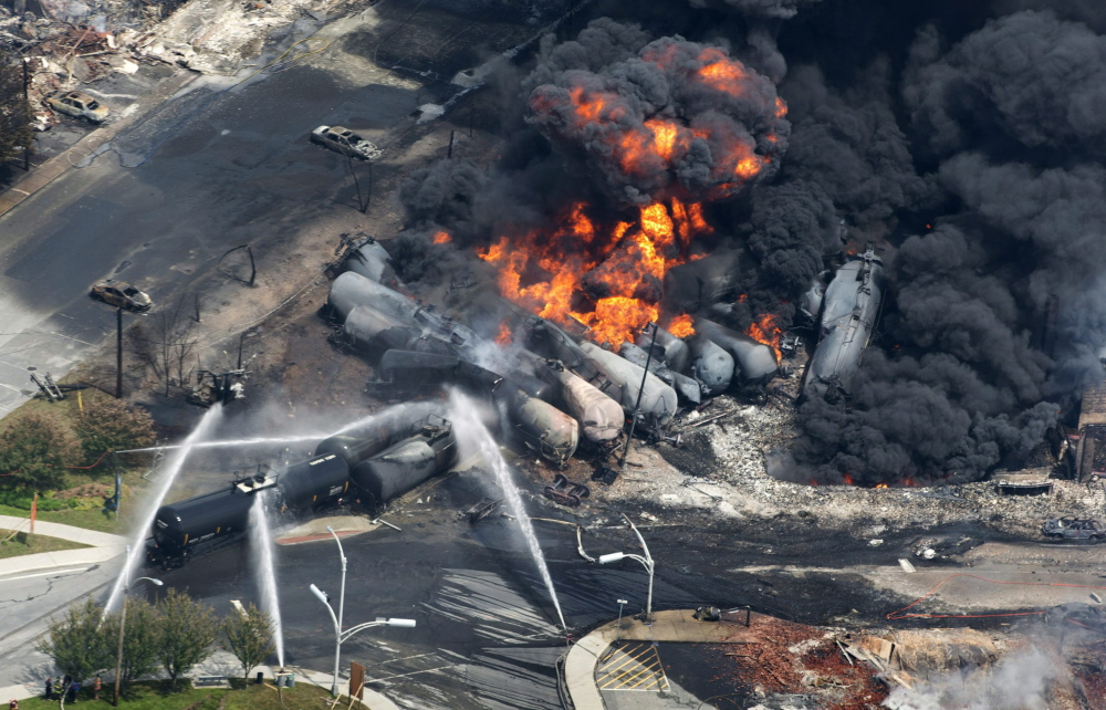 Smoke rises from derailed railway cars carrying crude oil in downtown Lac-Megantic, Quebec, on July 6, 2013. Lac-Megantic still struggles to recover as it marks the disaster's one-year anniversary.