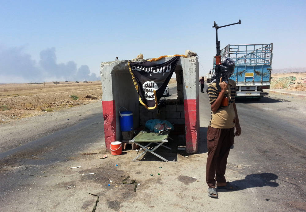 An al-Qaida-inspired militant stands guard last month at a checkpoint north of Baghdad that was captured from the Iraqi army.