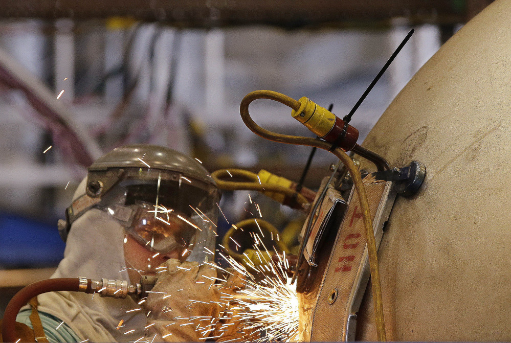 "A welder works on a ""compressed air flask"" that will eventually be installed in a Virginia-class nuclear-powered submarine at the Electric Boat company's Quonset Point facility in North Kingstown, R.I., this week. The shipyard has hired 2,000 workers in the last four years."
