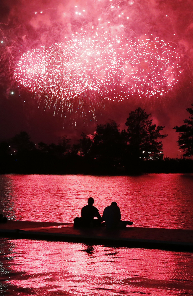 Fireworks explode over the Charles River in Boston on Thursday as boaters take in the scene.