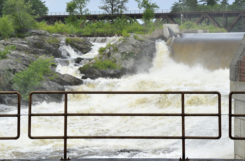 Raging water from the passing storm Friday night rush over the Great Falls in Lewiston.