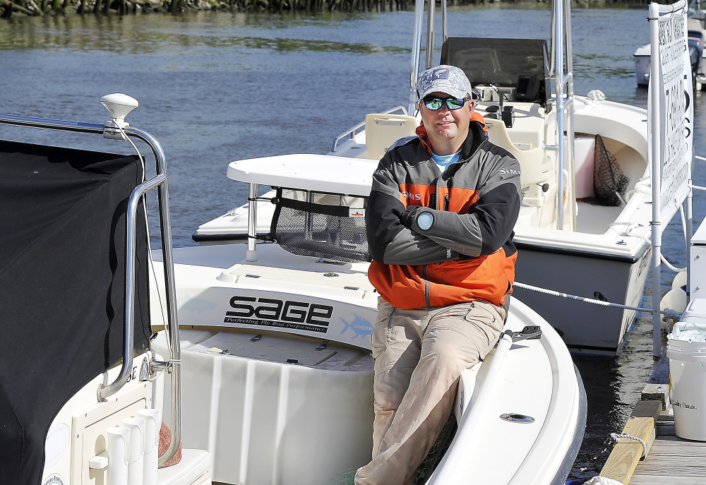 George Harris, a Maine Guide and fishing expert, relaxes on one of his two fishing boats tied up at the Kennebec Tavern Restaurant dock in Bath.