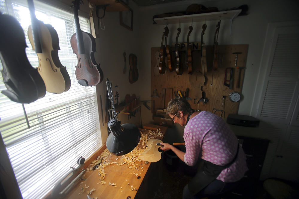 "Rose Clancy carves a flat section into a violin piece in her studio in Chatham, Mass. ""There's a real joy to making an instrument,"" she said, ""then using it to play music."" She founded the Chatham Fiddle Company three years ago and hosts concerts by top performers."
