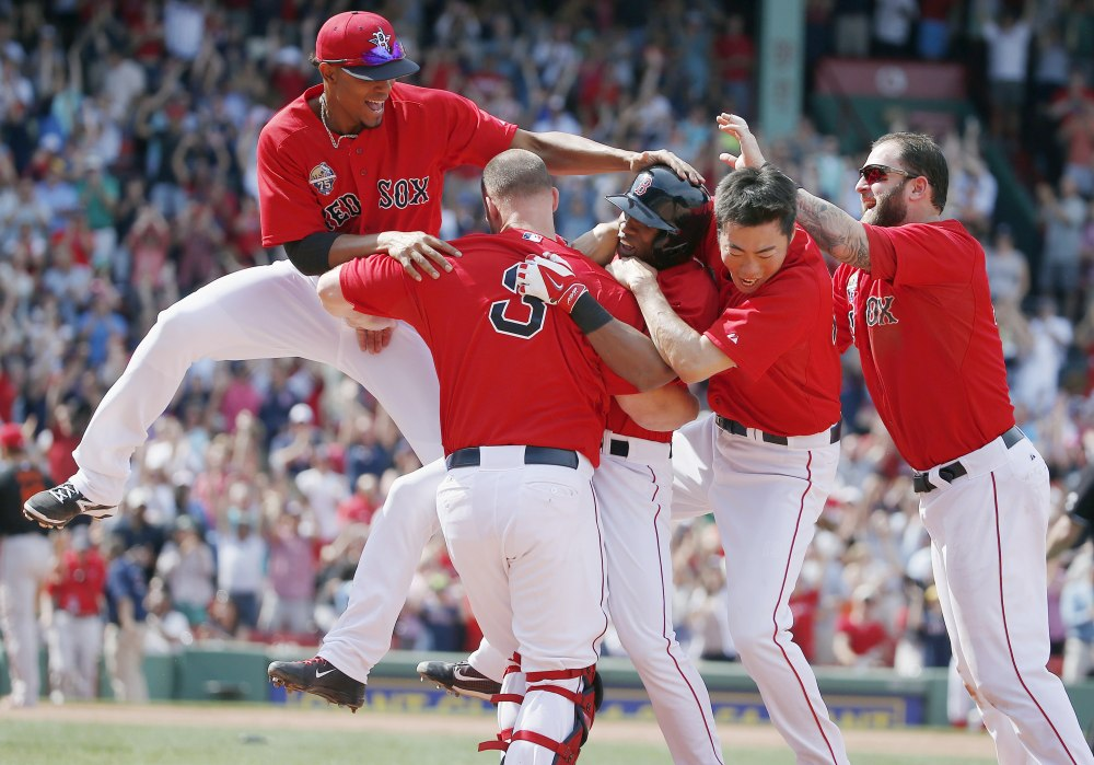 Boston Red Sox's Jonathan Herrera, center, celebrates his winning RBI single with teammates Xander Bogaerts, left, David Ross (3), Koji Uehara, second from right, and Mike Napoli, right, in the ninth inning of the first game of a doubleheader Saturday against the Baltimore Orioles in Boston. The Red Sox won 3-2.