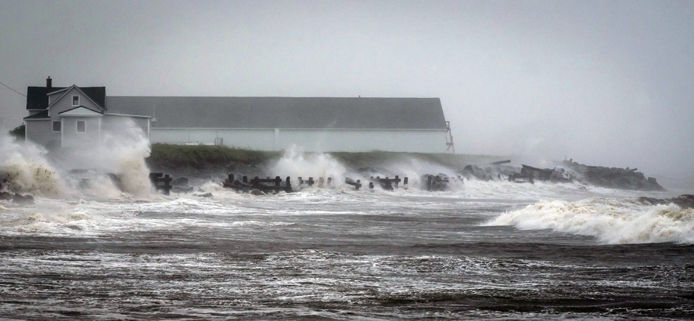 Waves crash against rock embankments that protect the Escuminac road against erosion during Tropical storm Arthur in Escuminac, New Brunswick, Saturday.