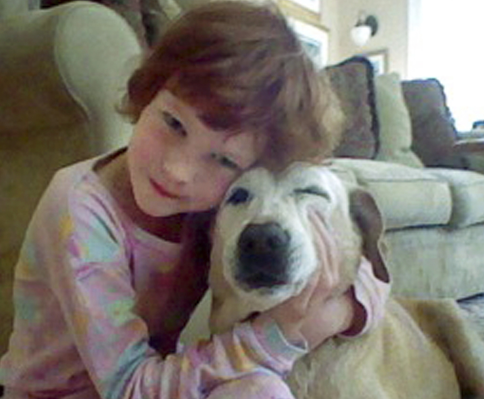 Catherine Violet Hubbard hugs her dog Sammy at home in Newtown, Conn., in 2012. Despite her death in the mass shooting at Sandy Hook Elementary School on Dec. 14, 2012, Catherine's dream of helping animals is close to becoming a reality. By early August, the state is expected to finalize transferring 34 acres of land for the new Catherine Violet Hubbard Animal Sanctuary.