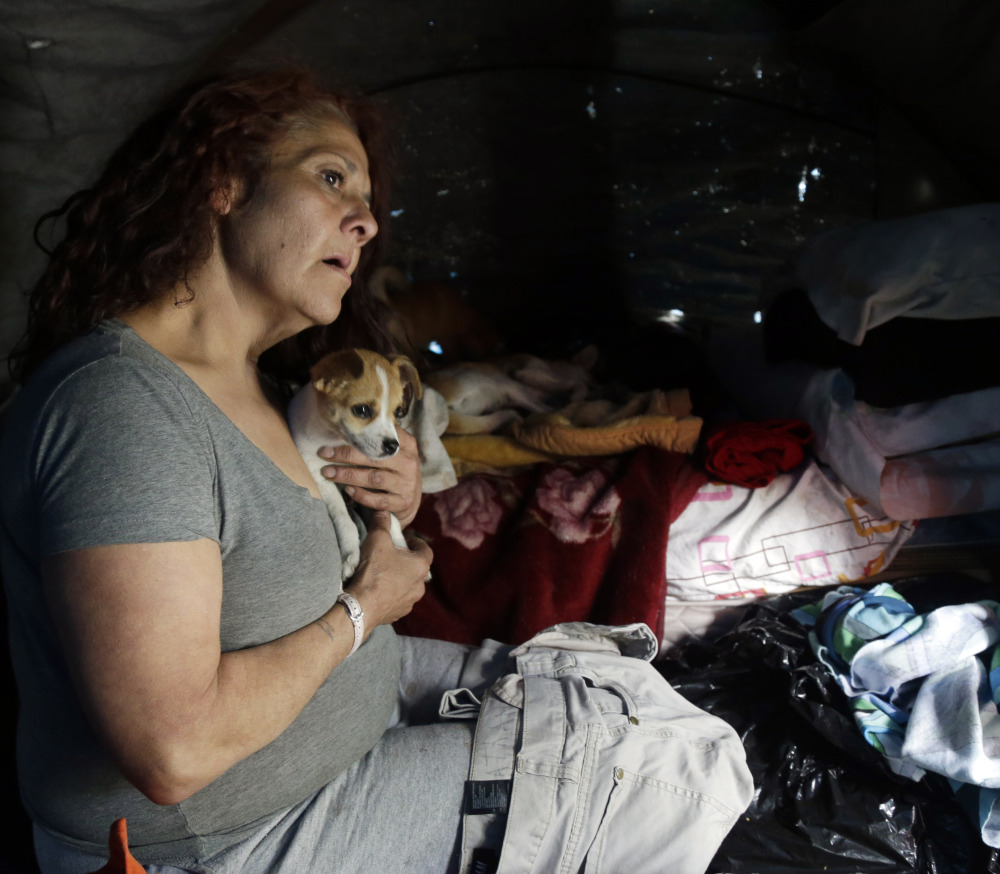 Maria Esther Salazar holds a dog in her tent in the Jungle, a homeless encampment in San Jose, Calif., last March. The Destination: Home pilot program works to place people like Salazar in their own apartments.