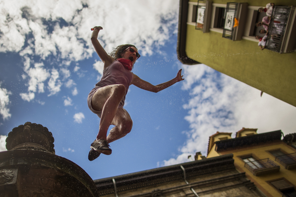 A reveler jumps from a fountain onto the crowd below, after the launch of the 'Chupinazo' rocket, to celebrate the official opening of the 2014 San Fermin fiestas in Pamplona, Spain, on Sunday.