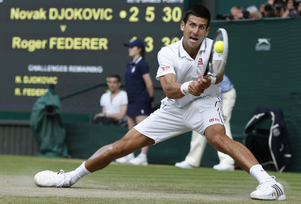 Novak Djokovic watches the ball hit his racket as he plays a return to Roger Federer during their men's singles final match Sunday at Wimbledon.