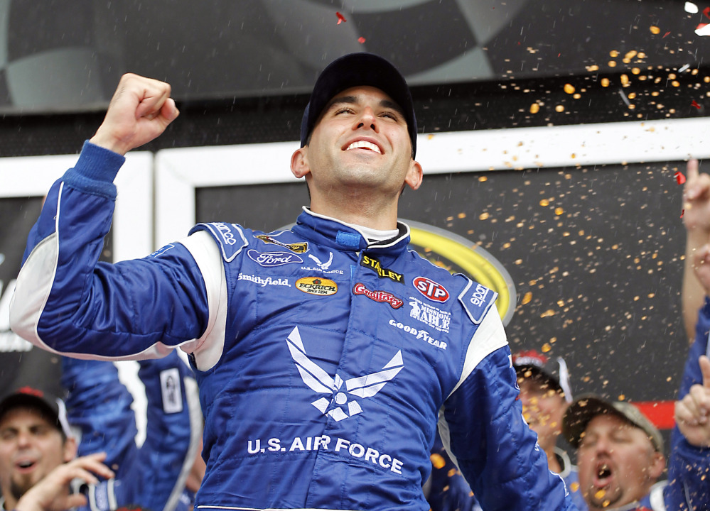 Aric Almirola celebrates in Victory Lane after winning the NASCAR Sprint Cup Series auto race at Daytona International Speedway in Daytona Beach, Fla., Sunday, July 6, 2014. (AP Photo/Terry Renna)