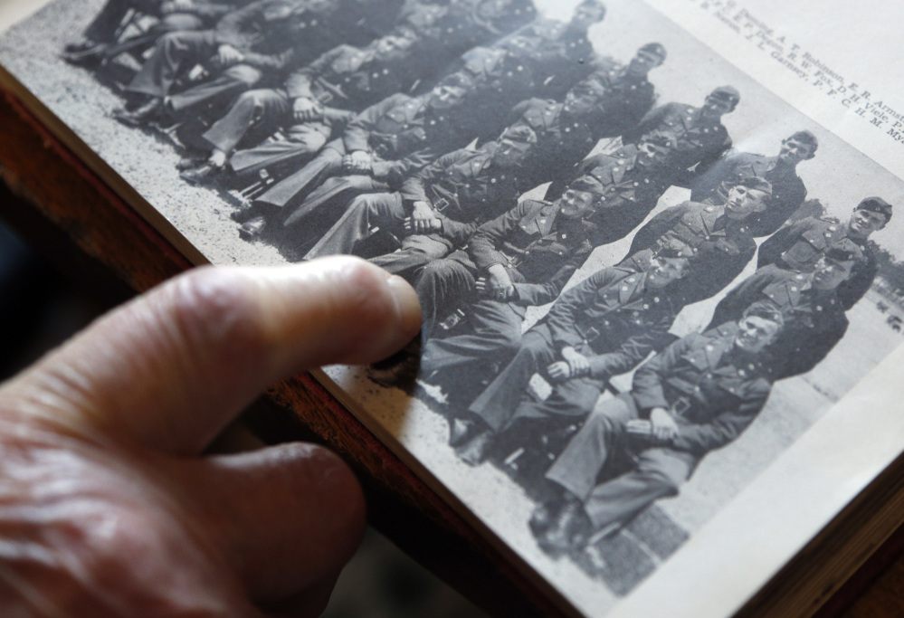 World War II veteran Arthur Robinson of Saratoga Springs, N.Y., points to himself in a 1940 photograph with his unit that lost many members in the fighting over Saipan.
