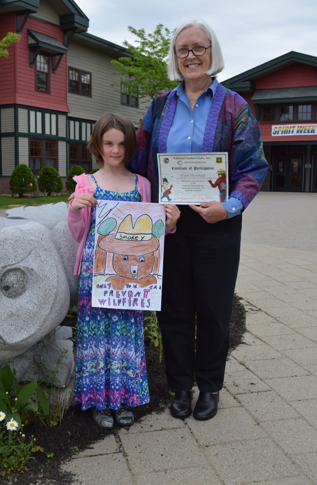 Wells Elementary School second-grader Logan Blanchard and Sandy Brennan, her art teacher, pose with Logan's poster submission, which won a New England competition.