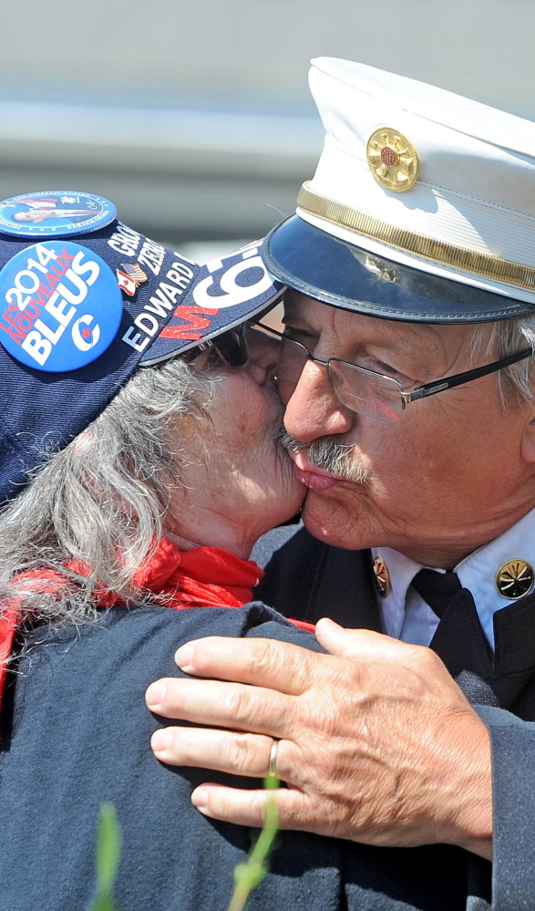 Rangeley Assistant Fire Chief Steve Grant gets a kiss from Lucille Gilbert of St. Georges Sunday in Lac-Megantic, Quebec.