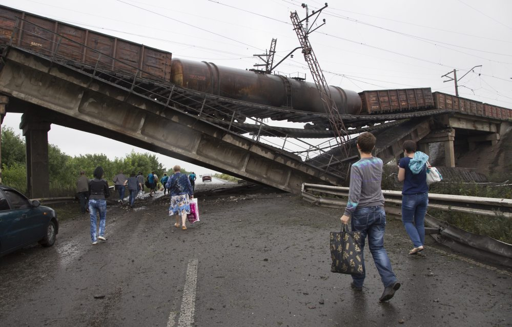 People walk under a destroyed railroad bridge over a main road leading into the east Ukraine city of Donetsk, near the village of Novobakhmutivka,  20 km North from the city of Donetsk, eastern Ukraine Monday.